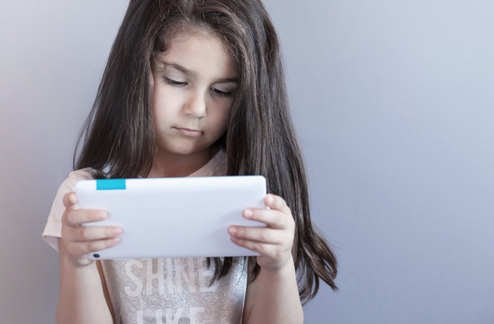 leisure, childhood, technology and people concept - child girl with tablet over lights background