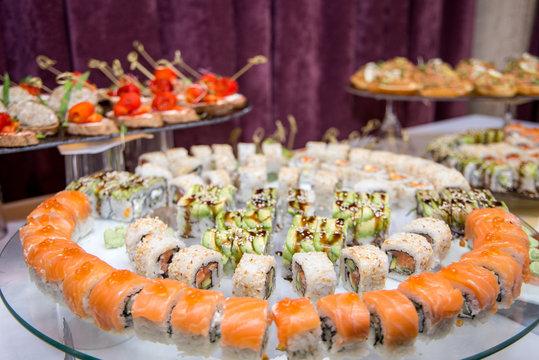 Japanese Cuisine -Buffet catering style Sushi Set in restaurant - salmon Maki Sushi and Nigiri Sushi. selective focus