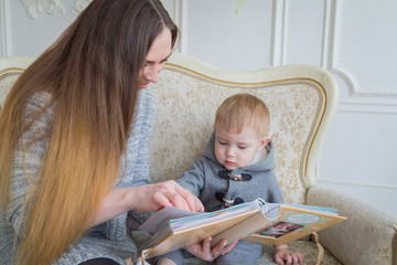 Mother and her baby son looking photobook