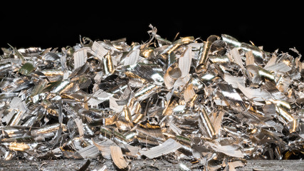 Tangle of glossy metal shavings. Close-up of the pile of manufacturing metallic chips on black background. Idea of industry, mechanical engineering, machining. Great depth of field.