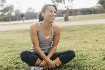 Cheerful young woman looking away while sitting with cross-legged on grassy field at park