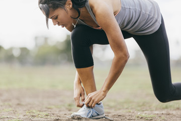Sporty young woman tying shoelace on field during workout at park