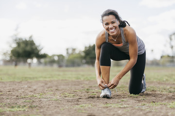 Young woman tying shoelace on field during workout at park
