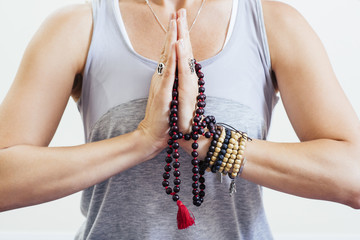 Midsection of mature woman with prayer beads doing meditation