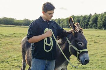 Teenage boy standing with donkey on farm