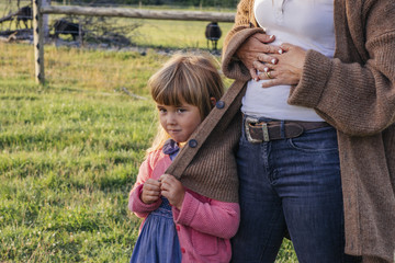 Cute little girl looking away while standing with mother on field