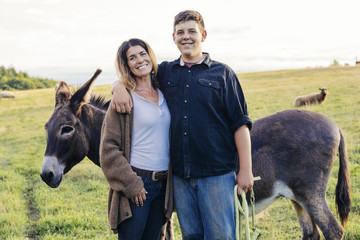 Portrait of smiling mother and son standing with donkey on farm