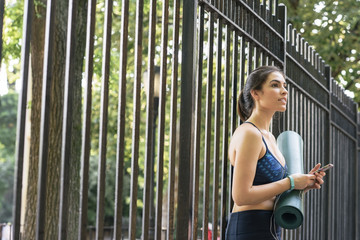 Side view of fit young woman with mobile phone and yoga mat standing against fence