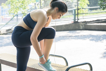 Fit young woman tying shoe on bench at park