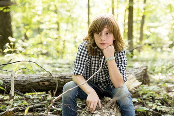 Thoughtful boy sitting on log in forest