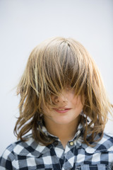 Portrait of boy with messy blond hair imitating as ghost over white background
