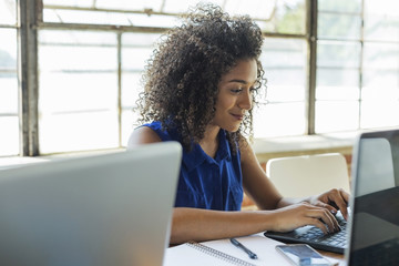 Confident young businesswoman using laptop at table in office