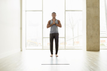 Young man meditating with hands clasped while standing on exercise mat