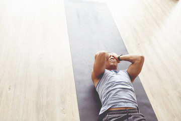 High angle view of young man lying on exercise mat while practicing yoga at health club