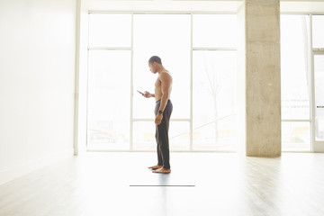 Shirtless young man using mobile phone while standing on exercise mat