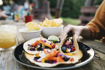 Closeup of woman's hand holding Mexican taco with vegetables at table