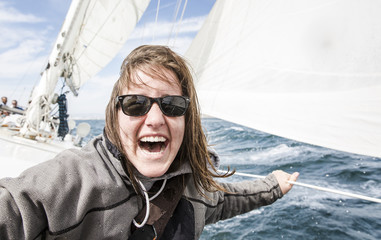 Happy young woman with sunglasses enjoying in sailboat over sea during sunny day