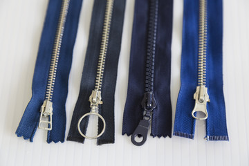 metal and plastic threaded blue zippers on the white background for textile concept.