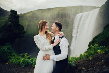 Happy stylish smiling couple walking and kissing in Iceland , on