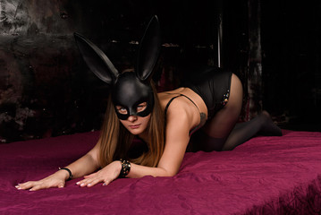 Sexy Bunny girl crawls on all fours on the bed with Burgundy sheets in a dark room