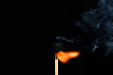 Match with weak flaring flame beveled on its side on a black background closeup