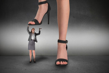 Composite image of female feet in black sandals standing on businesswoman
