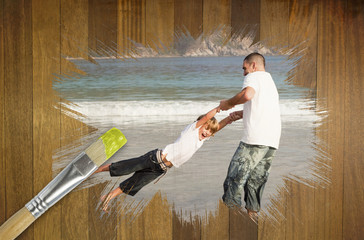 Composite image of father and son on the beach against wooden surface with paintbrushes