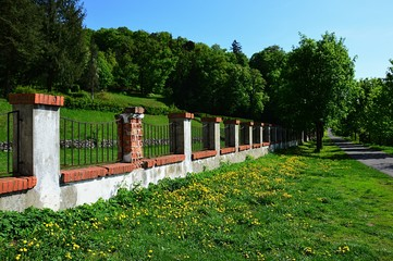 Line of brick decorative fence, road and trees leading from Svaty Anton mansion, Slovakia,  spring season.