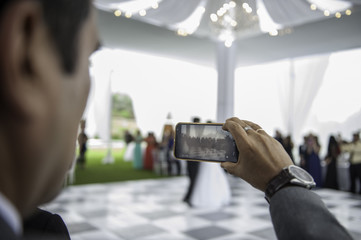 young man recording the bridal dance from his cell phone