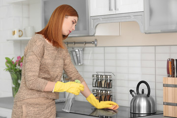 Tired housewife cleaning kitchen at home