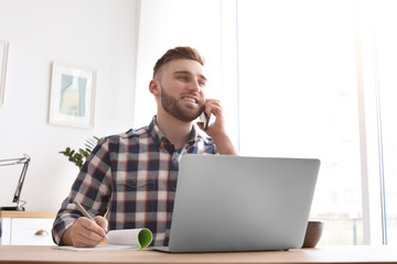 Young man talking on mobile phone while working with laptop at desk. Home office