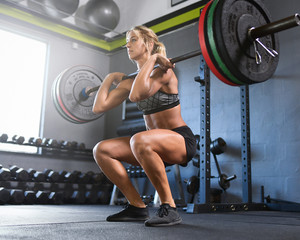 Woman doing barbell squat in the gym