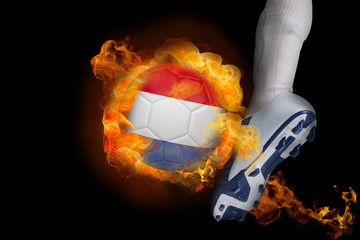 Football player kicking flaming netherlands ball against black