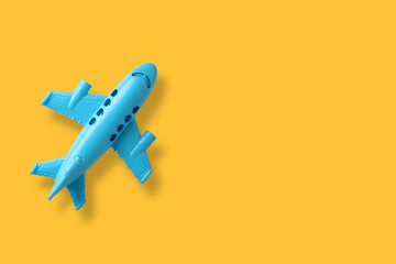 blue plastic toy plane on yellow background with space  Fototapete