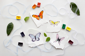 four watercolor pictures of butterflies on a white background with ornaments of ribbons