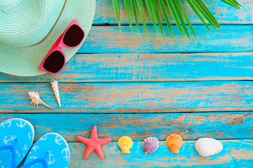 Summer background - Straw hat, sunglasses, slipper, starfish and shellsn on wood plank in blue sea paint color background.  Summer concept, Vintage retro styles