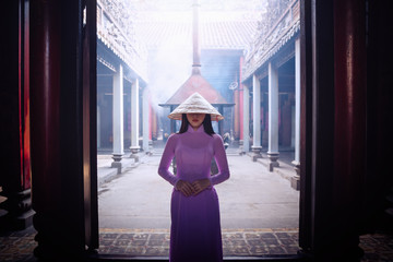 Young Vietnam woman wearing Ao Dai culture traditional at old temple in Vietnam,vintage style,travel and relaxing concept.