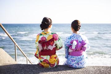 浴衣を着た女性たちは海辺に座っている