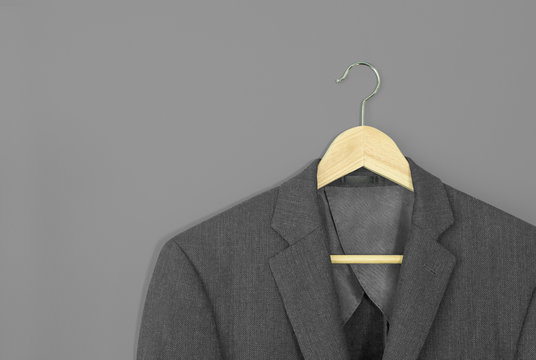 wood hanger with light grey suit isolated on grey background