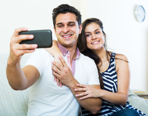 Positive young spouses posing and making selfie