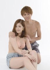 水着姿で寄り添う若いカップル