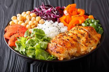 Organic Buddha bowl with raw vegetables, grilled chicken breast, chickpeas, rice and greens close-up on the table. horizontal