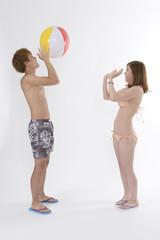 ビーチボールで遊ぶ若いカップル
