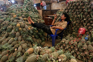 A worker rests beside piles of pineapple at the Kramat Jati wholesale market in Jakarta