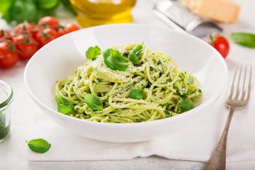 spaghetti pasta with basil pesto sauce and parmesan cheese on white bowl