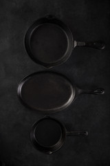 Monochrome concept. Black cast iron pans on black background