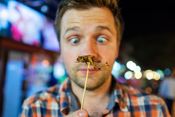 Caucasian young male eating cricket at night market in Thailand.