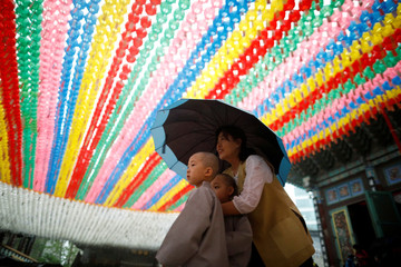 Novice monks walk underneath lotus lanterns bearing prayer petitions as they leave after an event to celebrate the upcoming Vesak Day in Seoul