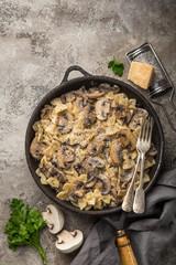 farfalle pasta with champignon mushrooms and garlic creamy sauce on pan
