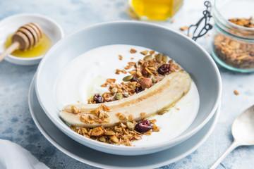 breakfast - yogurt with banana, homemade granola and honey in blue bowl